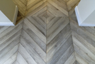 In the entry, gray chevron floor parquet (45°) is reversed in the middle of the room